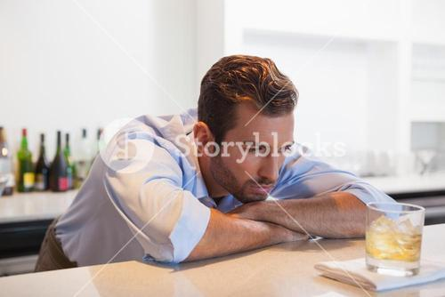 Drunk businessman staring at his whiskey glass