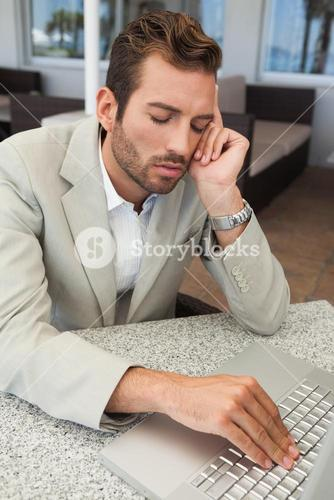 Exhausted businessman working with his laptop at table