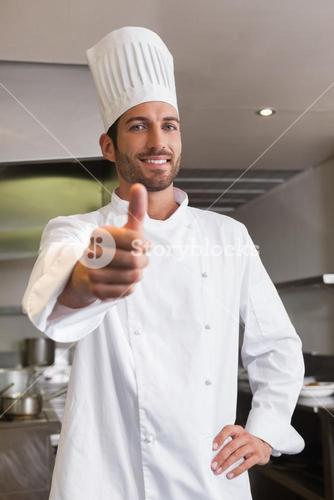 Happy young chef looking at camera showing thumb up