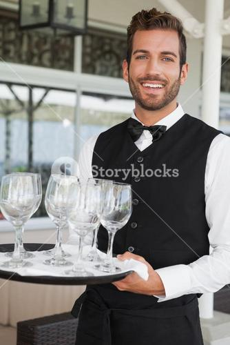 Handsome waiter holding tray of wineglasses