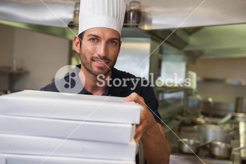 Happy pizza chef holding stack of pizza boxes