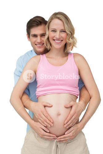 Expectant happy parents making a heart shape on mothers baby bump