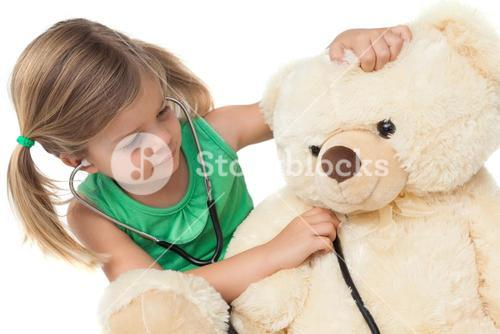 Cute little girl playing doctor with her teddy bear