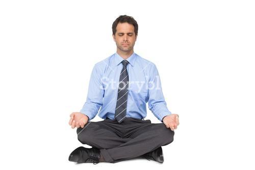 Zen businessman meditating in lotus pose with eyes closed