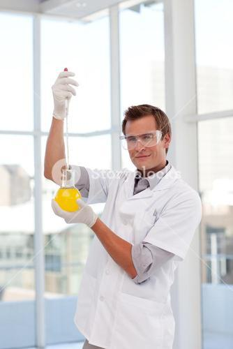 Scientist examining a testtube looking at the camera