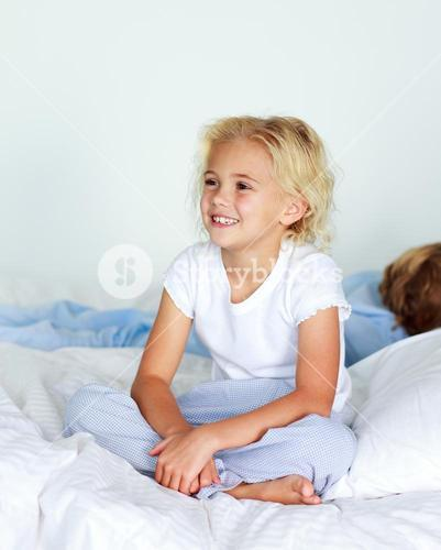 Little girl in bed smiling while her brother is sleeping