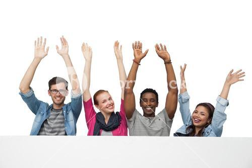 Portrait of four young friends raising hands