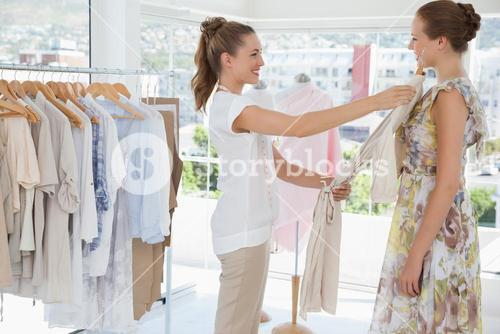 Saleswoman assisting woman with clothes at clothing store