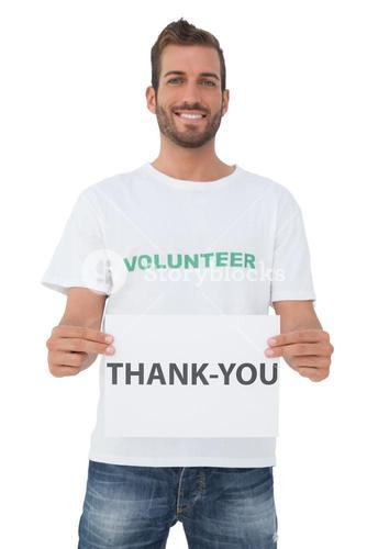 Smiling young male volunteer holding thank you' paper