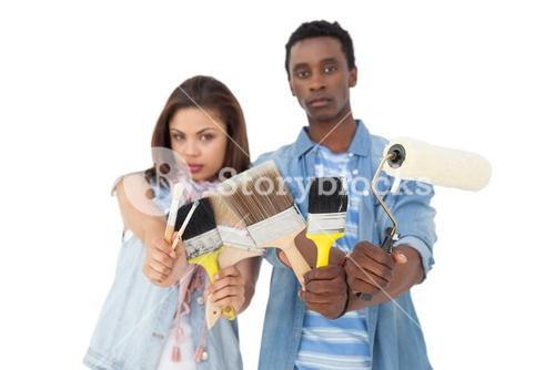 Portrait of a serious couple with painting tools