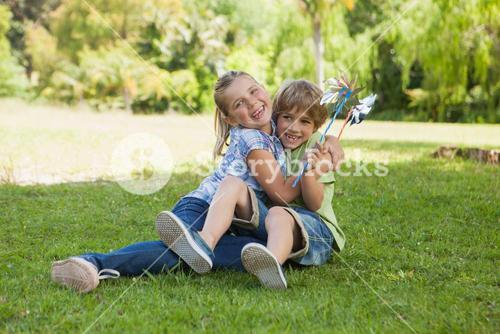 Two kids with pinwheels playing at park