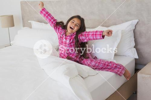 Girl yawning while stretching her arms in bed