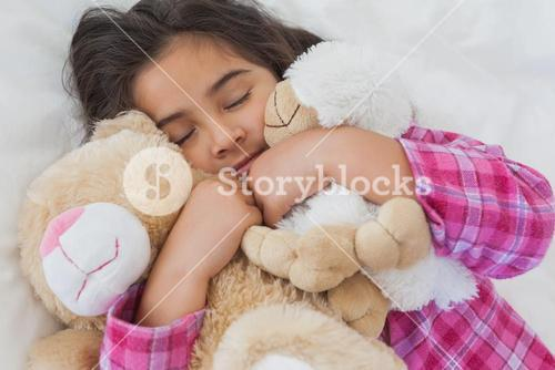 Girl sleeping with stuffed toys in bed