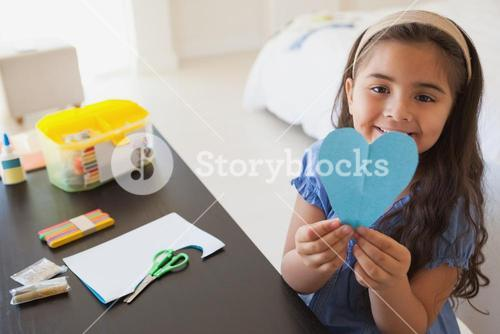 Cute young girl holding heartshape paper at table