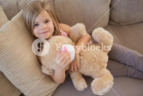 Portrait of a smiling girl with stuffed toy sitting on sofa