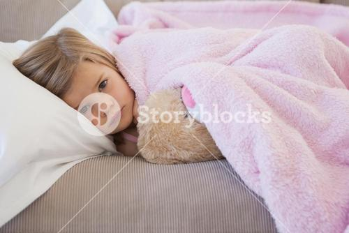 Young girl resting on sofa with stuffed toy