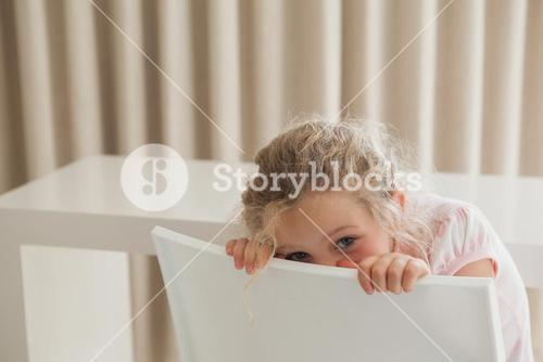 Cute girl hiding face behind chair
