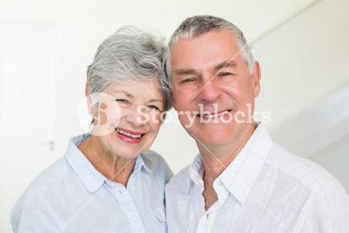 Happy retired couple smiling at camera