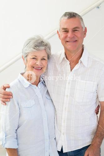 Happy retired couple standing and smiling at camera