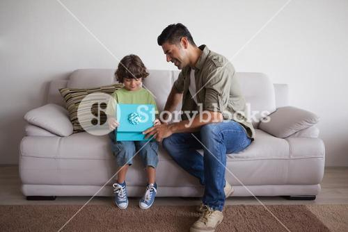 Father and son with gift box sitting in living room