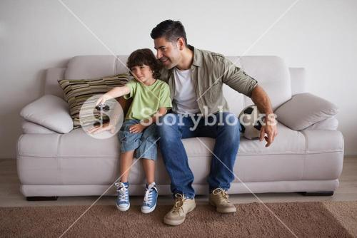 Father and son with football watching tv in the living room