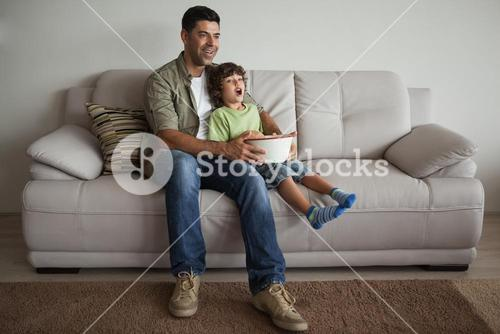 Father and son with popcorn bowl watching tv in the living room
