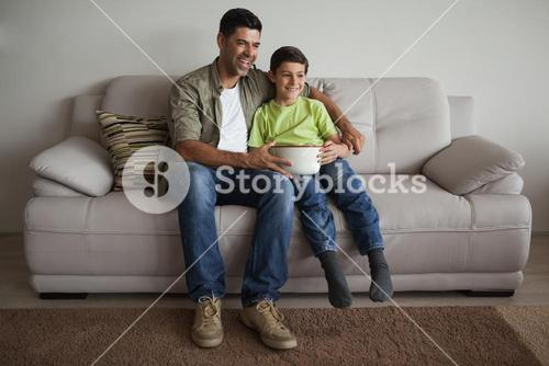 Father and son with popcorn bowl watching tv in living room
