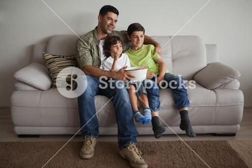 Father and sons with popcorn bowl watching tv in the living room