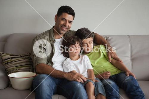 Father and sleepy sons with popcorn bowl watching tv in living room