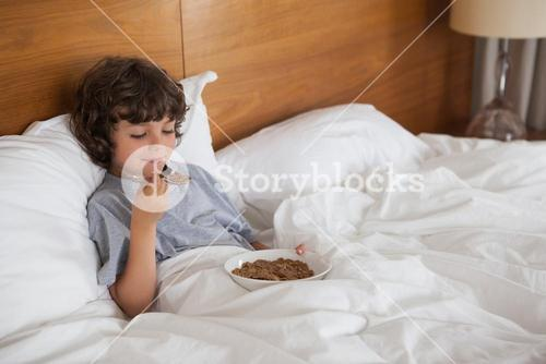 Young boy eating breakfast in bed