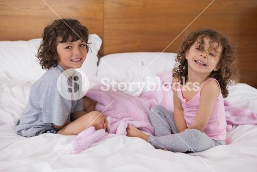 Portrait of happy siblings sitting in bed