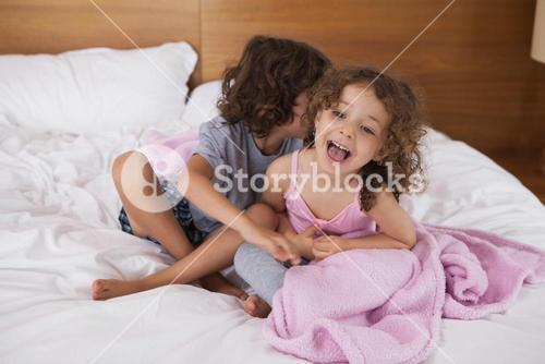 Happy siblings sitting in bed