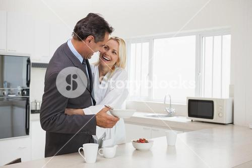 Woman embracing businessman in the kitchen