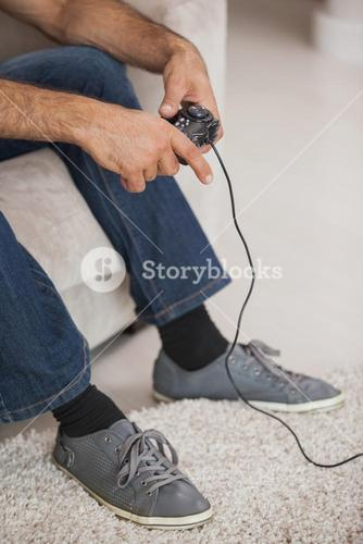 Low section of a man playing video games in living room