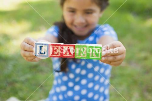 Happy girl holding block alphabets as learn at park