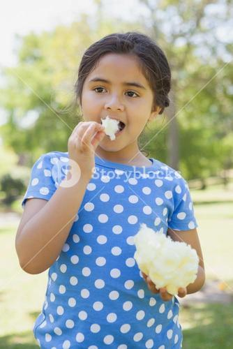 Beautiful girl eating cotton candy at park