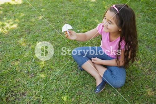 Happy girl playing with a paper plane at park