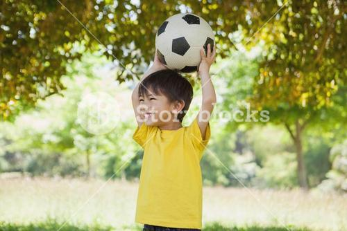 Little boy holding up football at park