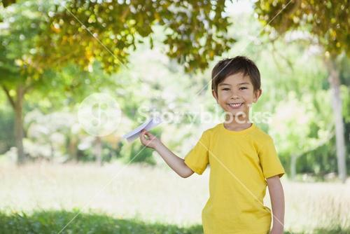 Happy boy playing with a paper plane at park