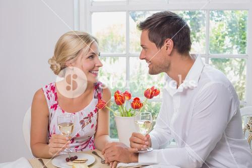 Happy young couple with wine glasses having food