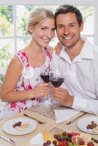 Loving young couple with wine glasses at dining table
