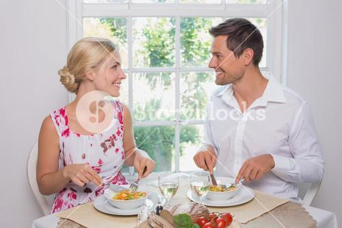 Loving couple looking at each other while having food