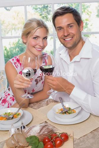 Loving couple with wine glasses sitting at dining table