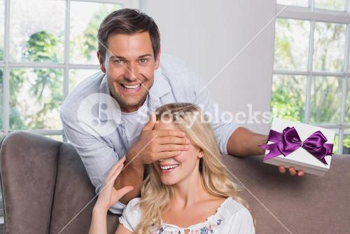 Young man surprising woman with a gift