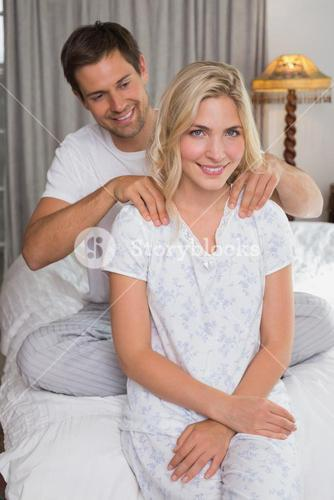 Man massaging womans shoulders in bed