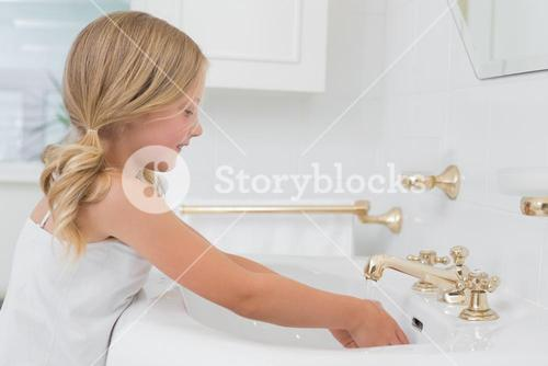 Side view of a cute girl washing hands at washbasin