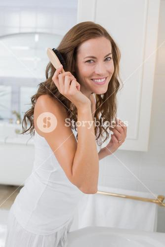 Portrait of a beautiful young woman brushing her hair