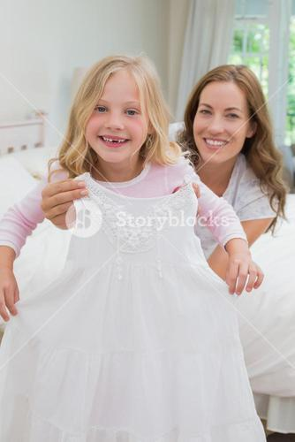 Mother trying new dress for her happy daughter