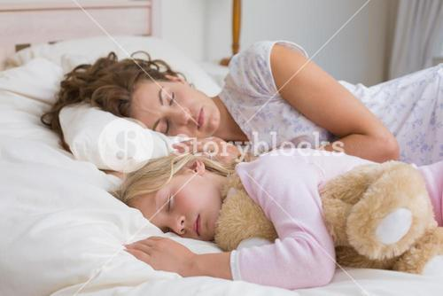 Girl and mother sleeping with stuffed toy in bed