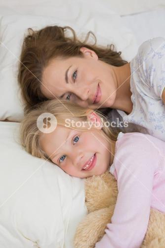 Girl and mother with stuffed toy resting in bed